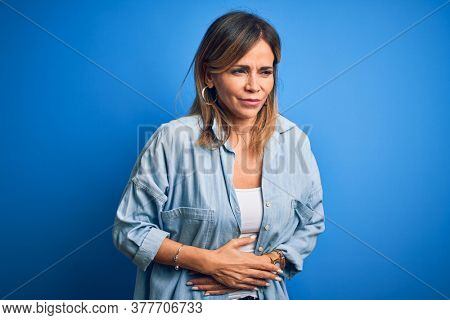 Middle age beautiful woman wearing casual shirt standing over isolated blue background with hand on stomach because indigestion, painful illness feeling unwell. Ache concept.