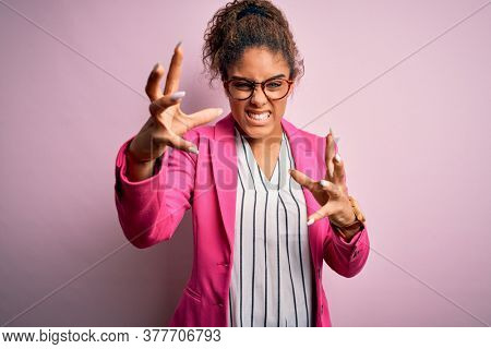 Beautiful african american businesswoman wearing jacket and glasses over pink background Shouting frustrated with rage, hands trying to strangle, yelling mad