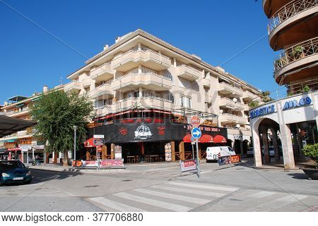 MAJORCA, SPAIN - NOVEMBER 12, 2019: Shops and tavernas on the seafront road at Port Alcudia on the Spanish island of Majorca. The resort is the main tourist destination in the North of the island.