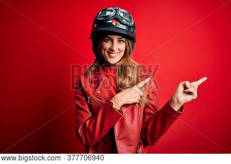 Young beautiful brunette motrocyclist woman wearing moto helmet over red background smiling and looking at the camera pointing with two hands and fingers to the side.