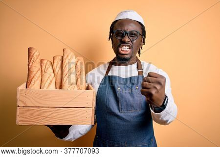 Young african american baker man wearing apron holding wooden box with homemade bread annoyed and frustrated shouting with anger, crazy and yelling with raised hand, anger concept