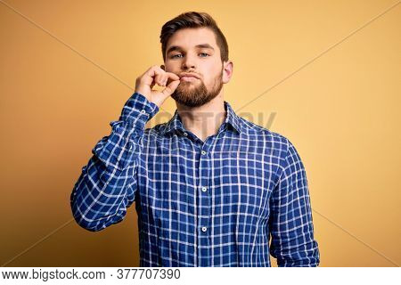 Young blond businessman with beard and blue eyes wearing shirt over yellow background mouth and lips shut as zip with fingers. Secret and silent, taboo talking