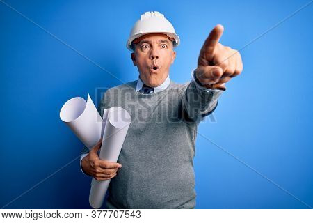 Middle age handsome grey-haired architect man wearing safety helmet holding blueprints Pointing with finger surprised ahead, open mouth amazed expression, something on the front