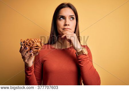 Young beautiful brunette woman holding bowl with germany baked pretzels serious face thinking about question, very confused idea