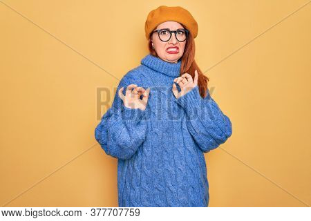 Young beautiful redhead woman wearing french beret and glasses over yellow background disgusted expression, displeased and fearful doing disgust face because aversion reaction. With hands raised