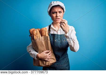 Young beautiful baker woman with blue eyes holding paper bag with  bread annoyed and frustrated shouting with anger, crazy and yelling with raised hand, anger concept
