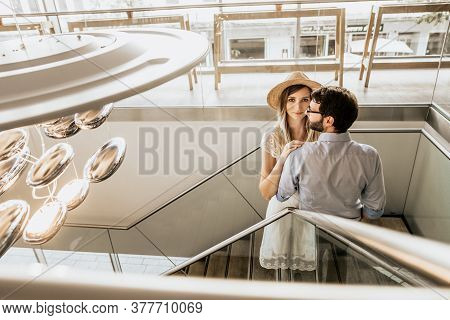 Stylish Couple On Stairs In Restorant. Happy Family Up Stairs And Woman In White Hat Look In Camera