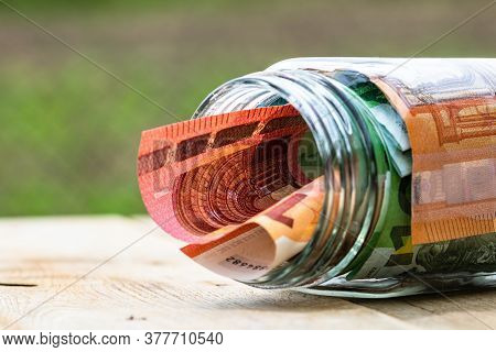 Composition With Saving Money Banknotes In A Glass Jar. Concept Of Investing And Keeping Money, Clos