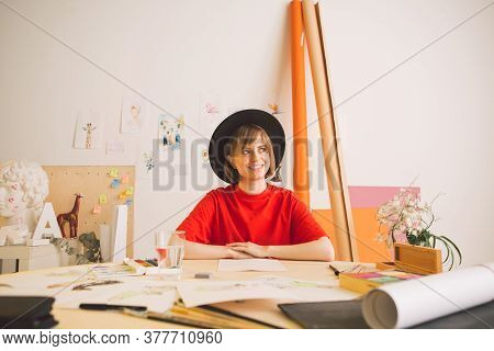 Young Happy Pretty Girl Artist In Hat Sitting At The Table In Studio. Photography About Inspiration