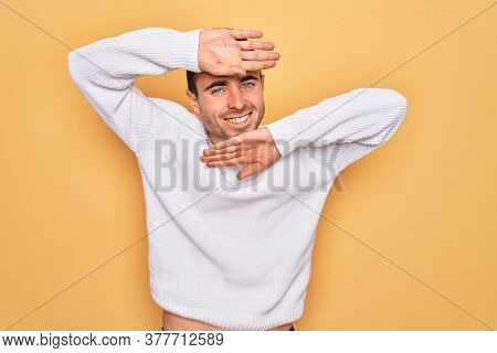 Young handsome man with blue eyes wearing casual sweater standing over yellow background Smiling cheerful playing peek a boo with hands showing face. Surprised and exited