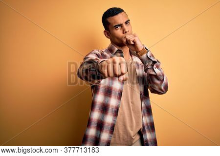 Young handsome african american man wearing casual shirt standing over yellow background Punching fist to fight, aggressive and angry attack, threat and violence