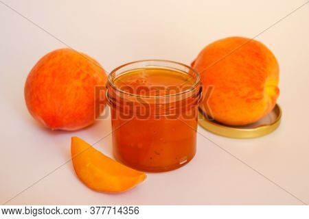 Fruit Jam. Open Glass Jar With Jam, Sliced Peaches And Whole Fruit On A Light Background. Concept Of