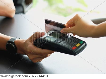 Man Using Credit Card Swipe Machine For Sell Products In The Shop To Customers. Concept Of Spending