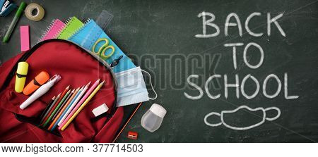 Backpack Full Of School Supplies On Green Blackboard With Protection Mask And Hydroalcoholic Gel Wit