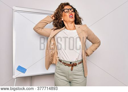 Middle age senior business woman standing on seminar presentation by magnectic blackboard Suffering of neck ache injury, touching neck with hand, muscular pain