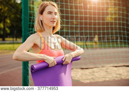 Healthy and wellness lifestyles concept. Woman prepare yoga mat outdoors. With sun flare.