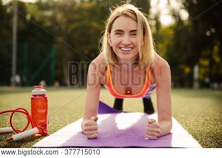 Beautiful young woman in sports wear doing plank exercise on yoga mat outdoor