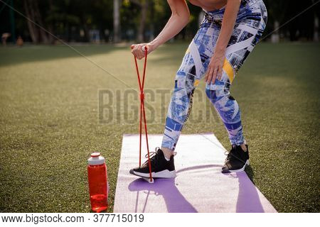 Cropped shot of woman during workout outdoor with a expander