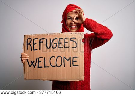 Woman wearing muslim hijab asking for immigration holding welcome refugees message with happy face smiling doing ok sign with hand on eye looking through fingers