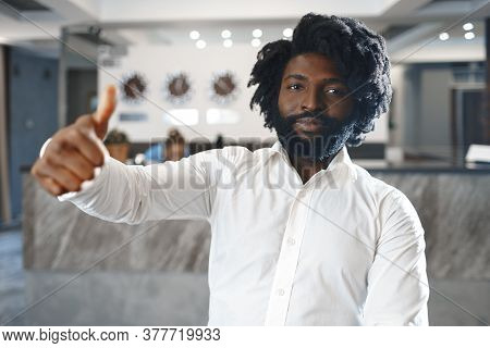 Portrait Of A Happy African Man Hotel Manager Or Guest Standing Against Hotel Front Desk