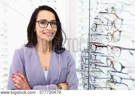 Sales Assistant Is Standing Next To An Optics Showcase. Stylish And Modern Glasses And Optics Concep