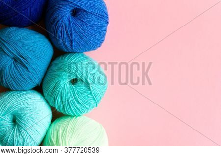 Acrylic Balls Of Yarn In Blue-green Shades On A Pink Background.  Nuance Color Combination. Skeins A