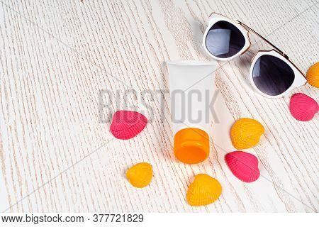 Sunblock Lotion With Colored Seashells On Wooden Board