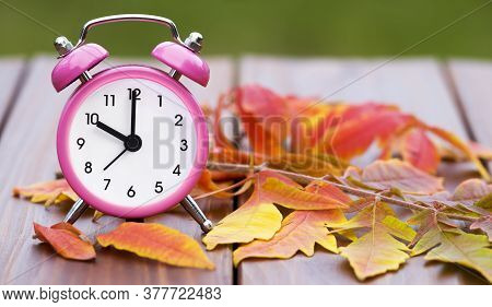 Daylight Savings Time In Autumn Fall, Retro Alarm Clock On A Wooden Background With Orange Leaves, W
