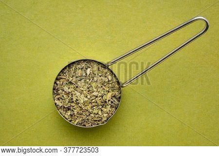 dried oregano leaf in a metal measuring scoop against handmade green paper