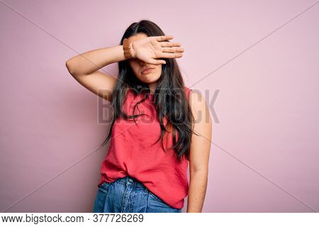 Young brunette woman wearing casual summer shirt over pink isolated background covering eyes with arm, looking serious and sad. Sightless, hiding and rejection concept
