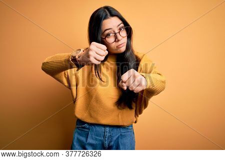 Young brunette woman wearing glasses and casual sweater over yellow isolated background Punching fist to fight, aggressive and angry attack, threat and violence
