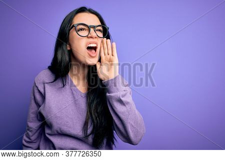 Young brunette woman wearing glasses over purple isolated background shouting and screaming loud to side with hand on mouth. Communication concept.