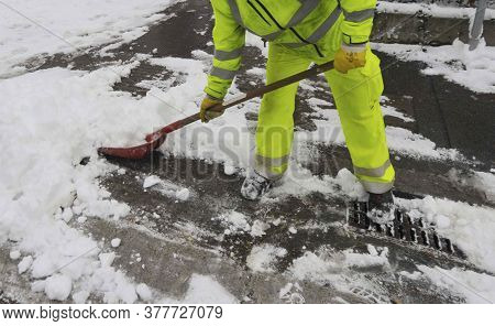 Worker At Snow Clearance With A Snow Shovel In Winter