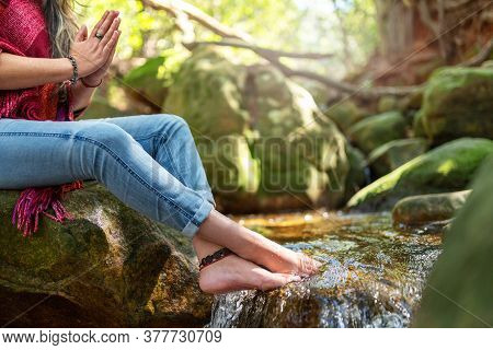 Closeup Of A Woman Praying With Her Hands Clasped On A Rock By A Small Stream In A Tranquil Forest