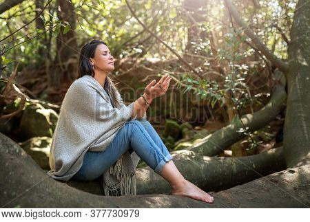 Woman Meditating Alone With Her Eyes Closed In A Tranquil Forest With The Palms Of Her Hands Raised