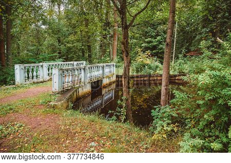 A Small Bridge Over A Creek In The Woods. The Architecture Of The 19th Century In The Classicism Sty