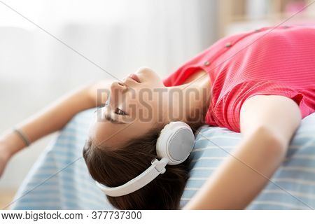 children and technology concept - portrait of smiling teenage girl in headphones lying on bed upside down and listening to music at home