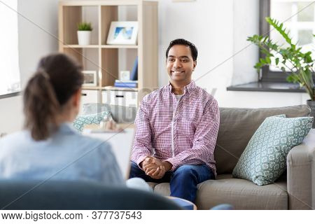 psychology, mental therapy and people concept - happy smiling young indian man patient and woman psychologist at psychotherapy session