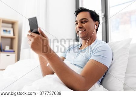 technology, bedtime and rest concept - happy smiling indian man in earphones with smartphone lying in bed and listening to music at home