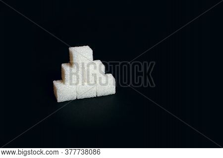 Six Sugar Cubes On A Black Background, A Sweet Additive To Taste Or A Harmful And Dangerous Ingredie