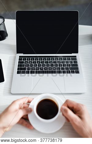 Cropped View Of Man Holding Coffee Cup Near Laptop With Blank Screen, Earning Online Concept