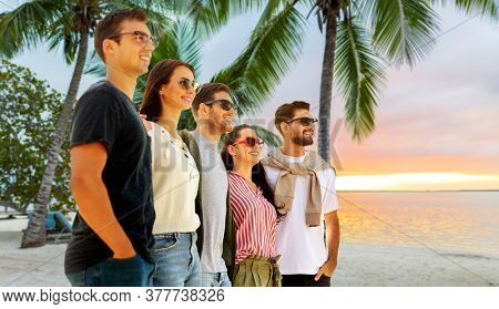 travel, tourism and vacation concept - group of happy friends over tropical beach background in french polynesia