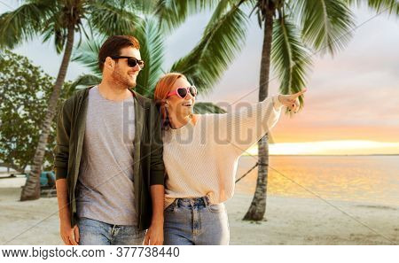 travel, tourism and vacation concept - happy couple walking over tropical beach background in french polynesia