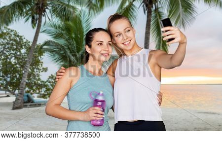 fitness, sport and healthy lifestyle concept - smiling young women or female friends taking selfie by smartphone over tropical beach background in french polynesia