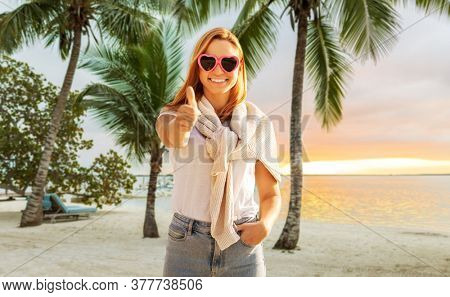 travel, tourism and vacation concept - happy woman in heart-shaped sunglasses showing thumbs up over tropical beach background in french polynesia