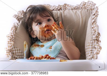 Adorable Little Funny Girl Of 12 Months Eating Spaghetti With Spoon While Sitting In High-powered Ch