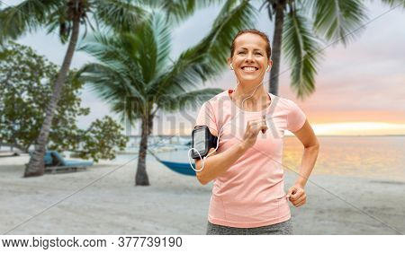 fitness, sport and healthy lifestyle concept - smiling woman with earphones wearing armband for smartphone, jogging and listening to music over tropical beach background in french polynesia