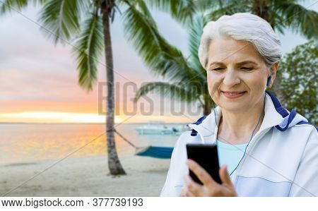 fitness, sport and healthy lifestyle concept - senior woman with earphones listening to music on smartphone over tropical beach background in french polynesia