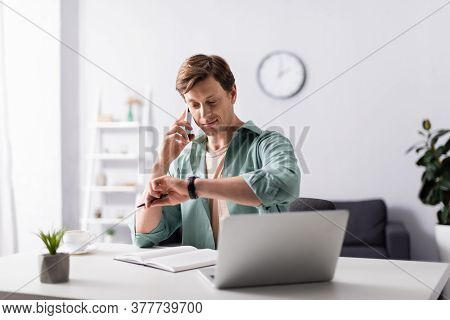 Selective Focus Of Man Checking Time While Talking On Smartphone Near Laptop And Notebook On Table,