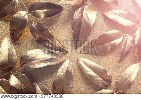 Abstract Golden Composition With Golden Leaves On Golden Sparkling Glitter Paper.